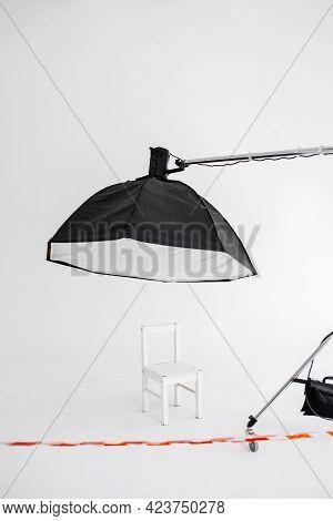 Preparation For Studio Shooting: Empty White Chair And Studio Lighting. Empty Studio Closed