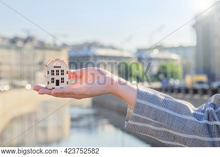 Small House On Hand Against The Background Of The City, Real Estate Agent Concept, Developers, Prefe