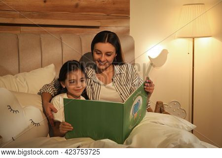 Little Girl With Mother Reading Book In Bedroom Lit By Night Lamp