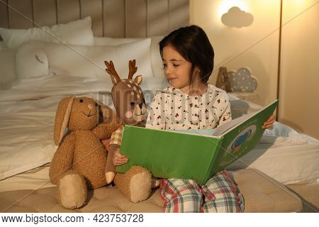 Little Girl Reading Book In Bedroom Lit By Night Lamp