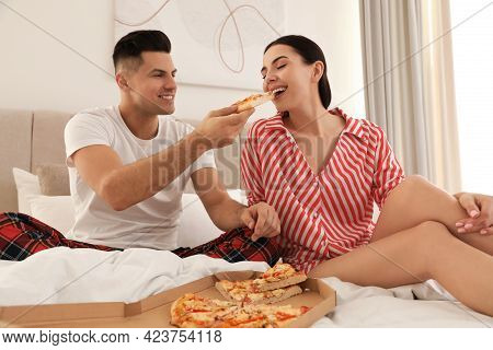 Happy Couple In Pyjamas Eating Pizza On Bed At Home
