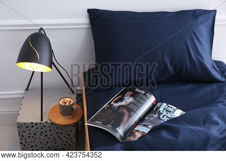 Open Magazine On Bed With Stylish Silky Linens