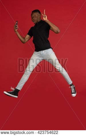 Always On Mobile. Full Length Of African Young Man Taking Phone While Jumping Against Red Studio Bac