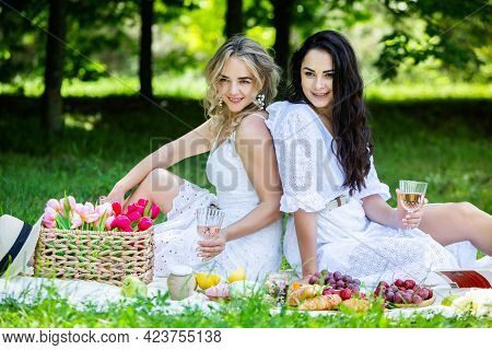 Two Girls Are Resting In Park Sitting On A Picnic Blanket. Friends Is Making Picnic Outdoor With Fru