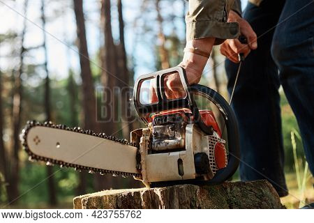Faceless Forester Starting Chainsaw For Cutting Trees In Forest, Planned Deforestation, Special Equi