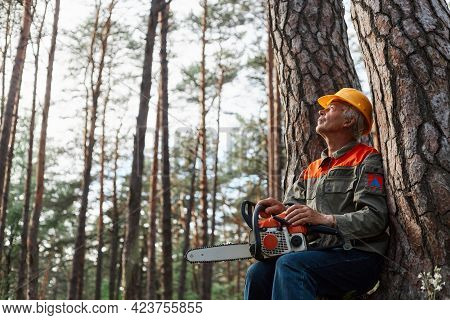Outdoor Shot Of Logger Having Rest In Open Air After Cutting Trees, Sitting Near Tree With Chainsaw