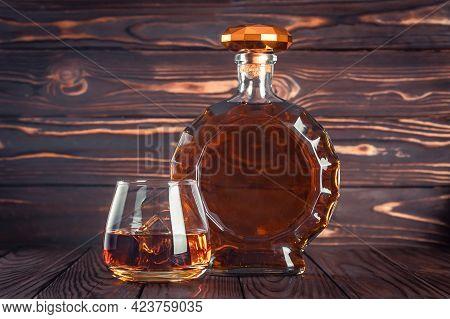 Glass And Bottle Of Whiskey. Decanter With Cognac On A Dark Brown Wooden Table. Brandy, Bourbon. Str