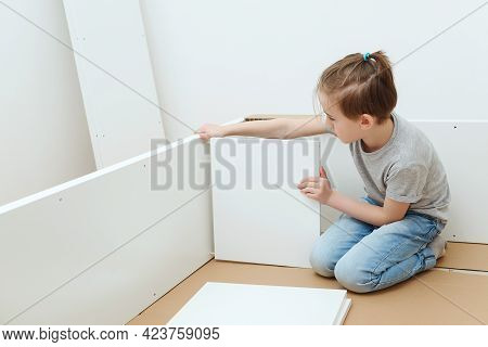 Boy Assembles A Bookshelf Hisself. Dad And Little Son Assembling Furniture At Home