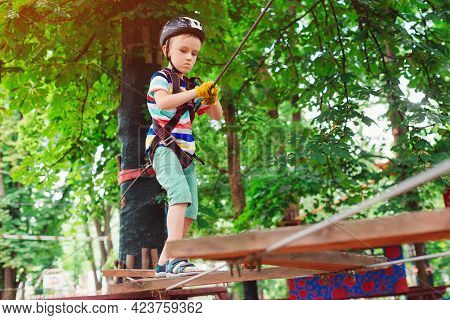The Boy Climbs A Rope Park. Little Cute Boy In A Climbing Adventure Park. Summer Sunny Day. Rope Pla