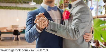 lgbt, homosexuality and same-sex marriage concept - close up of happy male gay couple holding hands and dancing on wedding over restaurant background