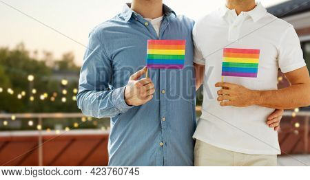 lgbt, homosexuality and people concept - close up of happy male gay couple hugging and holding rainbow flags over roof top party background