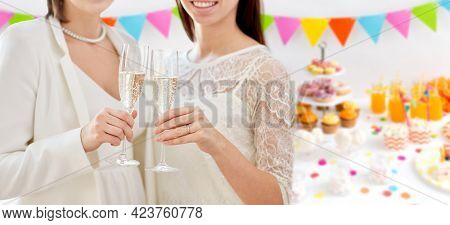 homosexuality, same-sex marriage and lgbt concept - close up of happy married female gay couple holding and clinking champagne glasses on wedding over party background