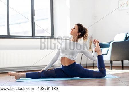 fitness, people and healthy lifestyle concept - young woman doing splits yoga pose at studio