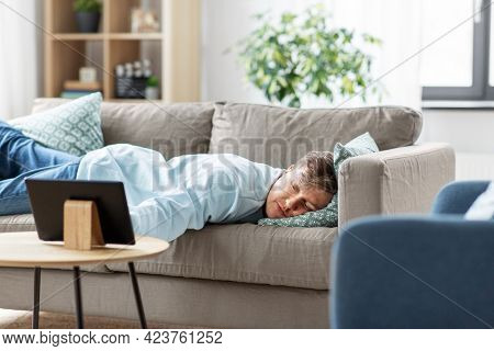 people, boredom and depression concept - bored or lazy young man with tablet pc computer lying on sofa at home