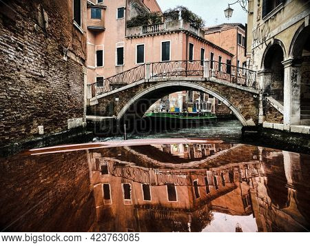 Reflection of the houses on the Varnished wooden hood, pontoon, of the water taxi in the streets of Venice, which leaves