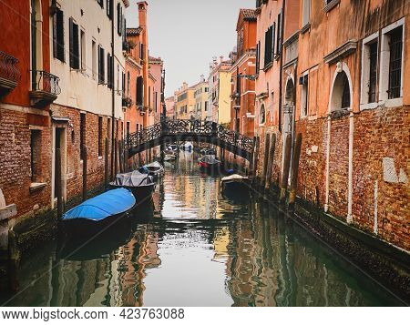 Boats docking close to a Beautiful small bridge in Venice. Toned image