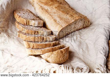 Sliced Bread On Linen Towel. Top View Of Sourdough Bread. Traditional Leavened Bread Baking Method.
