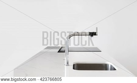 White Clean Kitchen Counter With Modern Shiny Faucet And Square Metal Sink With Built-in Glass Stove