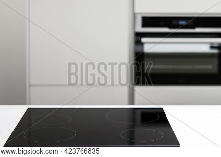White Countertop With Glossy Built In Ceramic Black Induction Stove, Big White Cupboard With Built-i