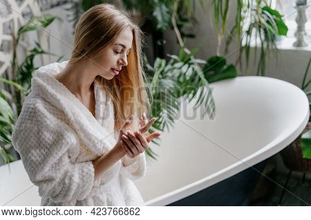 Concept Of Home Spa And Natural Skincare Cosmetics. Smiling And Dreamy Young Woman In White Soft Bat