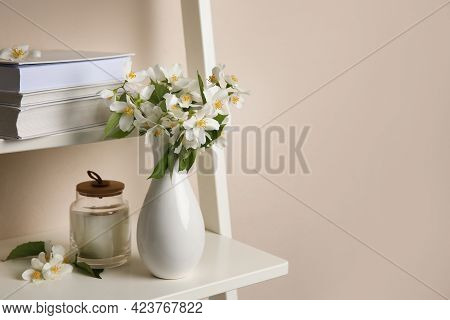 Bouquet Of Beautiful Jasmine Flowers In Vase And Candle On Shelving Unit Near Beige Wall Indoors, Sp