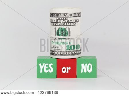 A Roll Of Paper Money, Colored Cubes And The Word Yes Or No