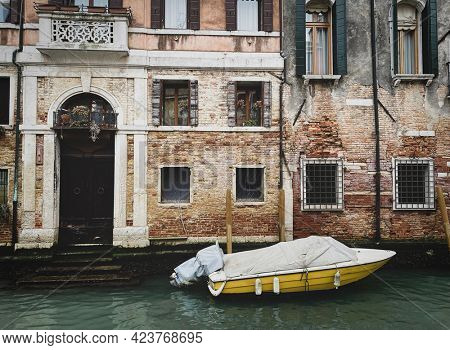 Side view of a yellow boat docking in front of a old red bricks venetian house, toned image