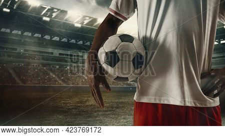 Cropped Male Soccer, Football Player Standing With Ball At The Stadium During Sport Match On Light S