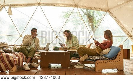Smiling Young Multiracial Freelance Team Working Together Using Digital Gadgets While Sitting Comfor