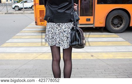 Pedestrian Girl Waiting For The Signal To Cross The Road At A Pedestrian Crossing On Sunny Summer Da
