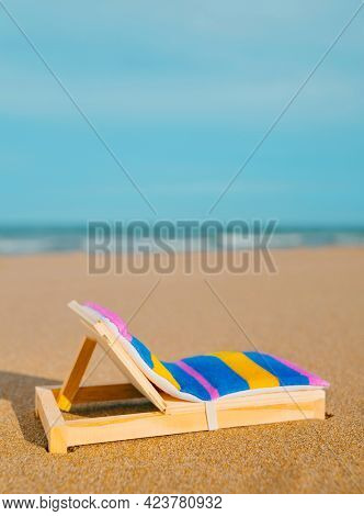 a miniature deck chair on the sand of a lonely beach, with the sea in the background and some blank space on top