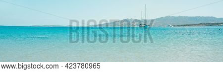 a sailboat and a yacht are sailing on the calm water of the Mediterranean sea in Sardinia, Italy, seen from Spiaggia di Vena Longa, in a panoramic format to use as web banner or header