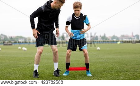 Teenage Boy With Soccer Coach On Stretching Session. Young Football Player Training With Stretching