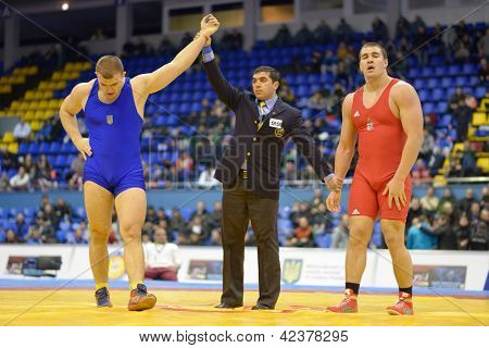 KIEV, UKRAINE - FEBRUARY 16: Khotsianivskyi, Ukraine win the match with Ligeti, Hungary during International freestyle wrestling and woman wrestling tournament in Kiev, Ukraine on February 16, 2013