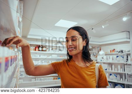 Portrait Of Smiling Young Woman In Drugstore Standing Against Shelf Picking Medicine