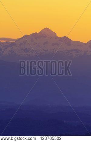 Triglav, The Highest Alpine Peak In Slovenia During Twilight Time With Intensely Orange Sky In Backg