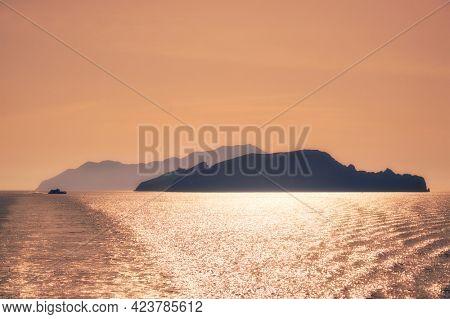 High speed catamaran vessel and Cyclades greek islands silhouettes in Aegean sea. Greece