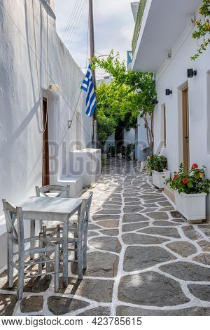 Picturesque narrow street with traditional whitewashed houses with greek flag of Naousa town in famous tourist attraction Paros island, Greece