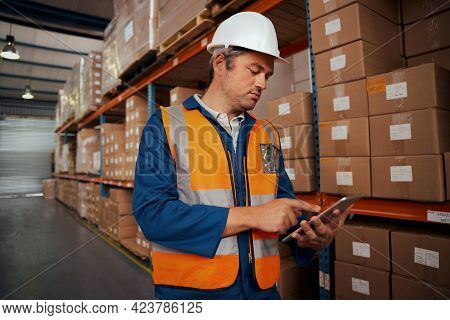 Portrait Of A Male Warehouse Supervisor In White Hardhat Using Digital Tablet In Factory