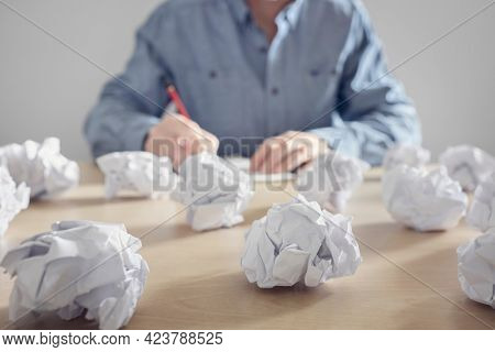 Frustration stress and writers block, business man with crumpled paper balls in a pile