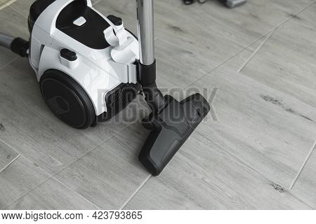 Bagless Cyclone Vacuum Cleaner On A Grey Tile. Electrical Apparatus That By Means Of Suction Collect