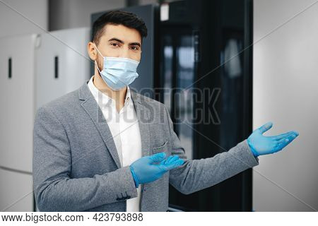 Asian Salesman Wearing Mask In Household Appliance Store Presenting New Model Of Refrigerator