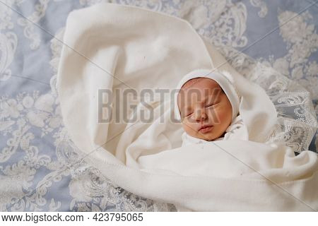 Newborn Baby Sleeps In White Clothes. Attire For Discharge From The Hospital.