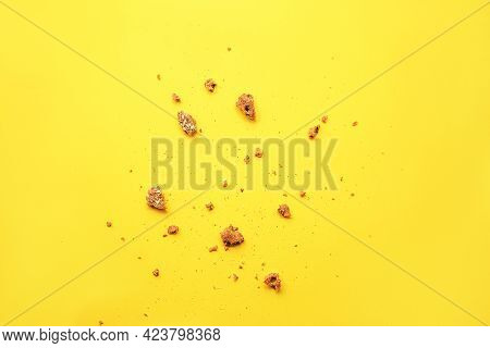 Scattered Crumbs On Bright Yellow Background, Top View.