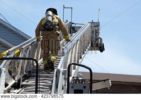 Firefighter Climbing A Ladder Fireman At Work Extinguishing Fire