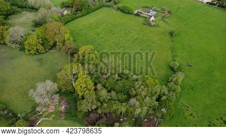 An Aerial View Over Open Countryside With Hedgerows And Rolling Fields