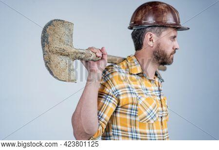 Shovel In Hand Of Man Laborer. Guy Wear Worker Uniform. Handsome Builder In Helmet.