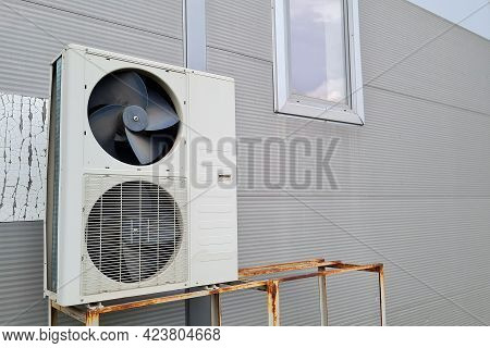 White Double Outdoor Unit Of Air Conditioner On Gray Wall Of Shopping Center. One Of Fans Without A