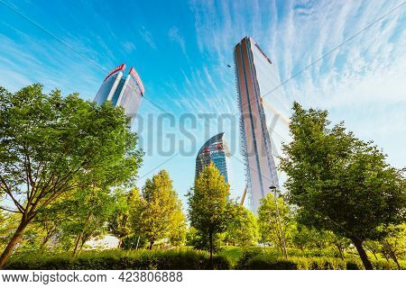 Milan, Italy - May 2021: View Of Citylife Skyscrapers, Milan With Blue Sky And Green Trees