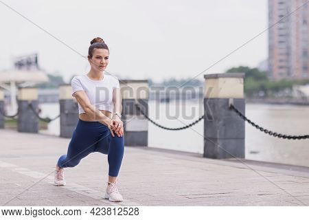 Runner Stretching Muscles Outdoor At Summer Morning In City. Running Athlete Woman Doing Fitness Str